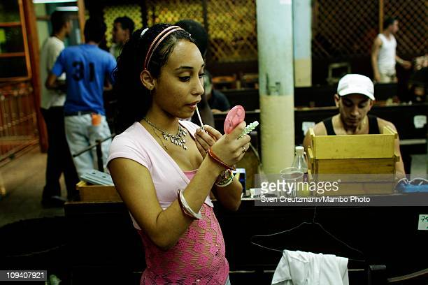 A tobacco worker puts on makeup before before leaving for lunch break in the Partagas cigar factory in Old Havana during the 13th Habanos Festival on...