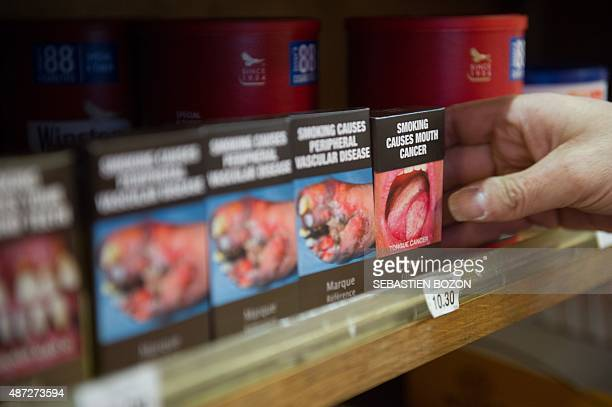 A tobacconist installs factitious neutral cigarette packaging in a tobacco shop during a national day of protest by French tobacconnists against...