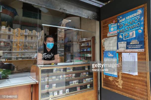 Tobacconist protected by plexiglass panels in front of his shop, the first day after the end of the lockdown imposed by the Italian government due to...
