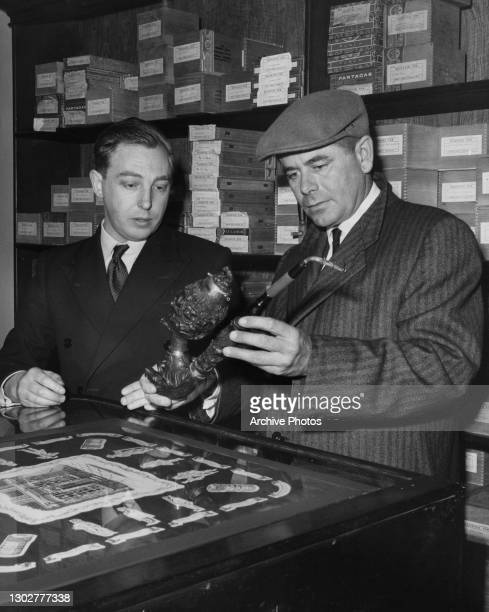 Tobacconist shows a 230 years old hand-carved pipe to Canadian-American actor Glenn Ford inside the British snuff manufacturer and retailer Fribourg...