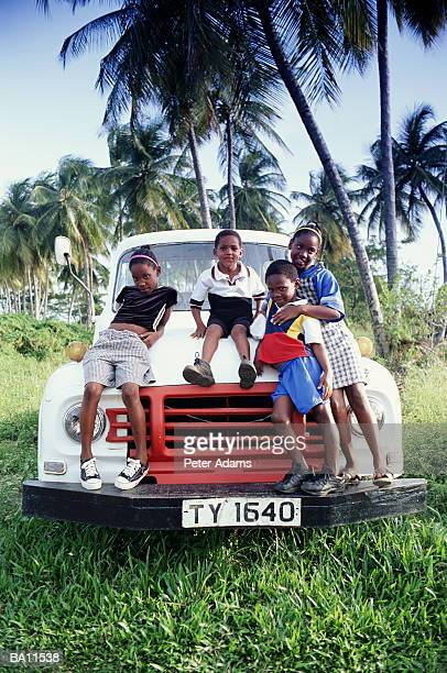 tobago, four native children sitting on hood of car - trinidad and tobago stock pictures, royalty-free photos & images