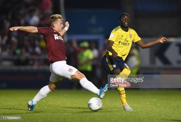 Tobi Omole of Arsenal passes the ball under pressure from Sam Hoskins of Northampton during the Leasingcom match between Northampton Town and Arsenal...