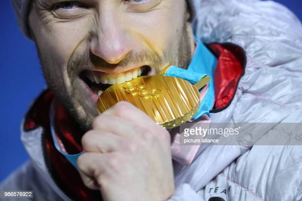 Tobias Arlt from Germany biting his gold medal during the award ceremony of the team luge event of the 2018 Winter Olympics in Pyeongchang South...