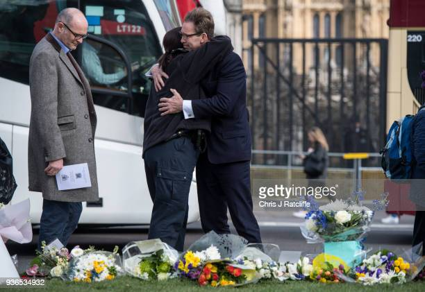 Tobias Ellwood embraces a female police officer next to floral tributes in Parliament Square on the first anniversary of the Westminster Bridge...