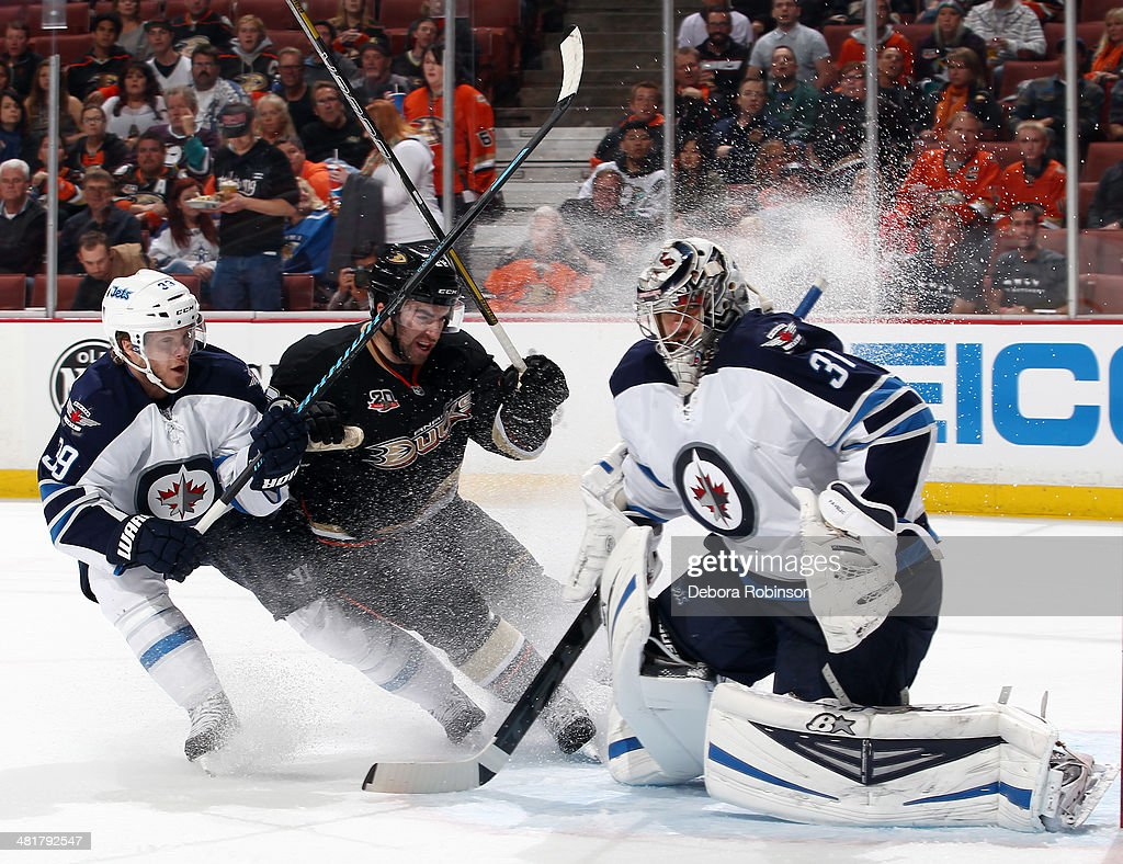 Tobias Enstrom #39 and Ondrej Pavelec #31 of the Winnipeg Jets defend the net against Kyle Palmieri #21 of the Anaheim Ducks on March 31, 2014 at Honda Center in Anaheim, California.