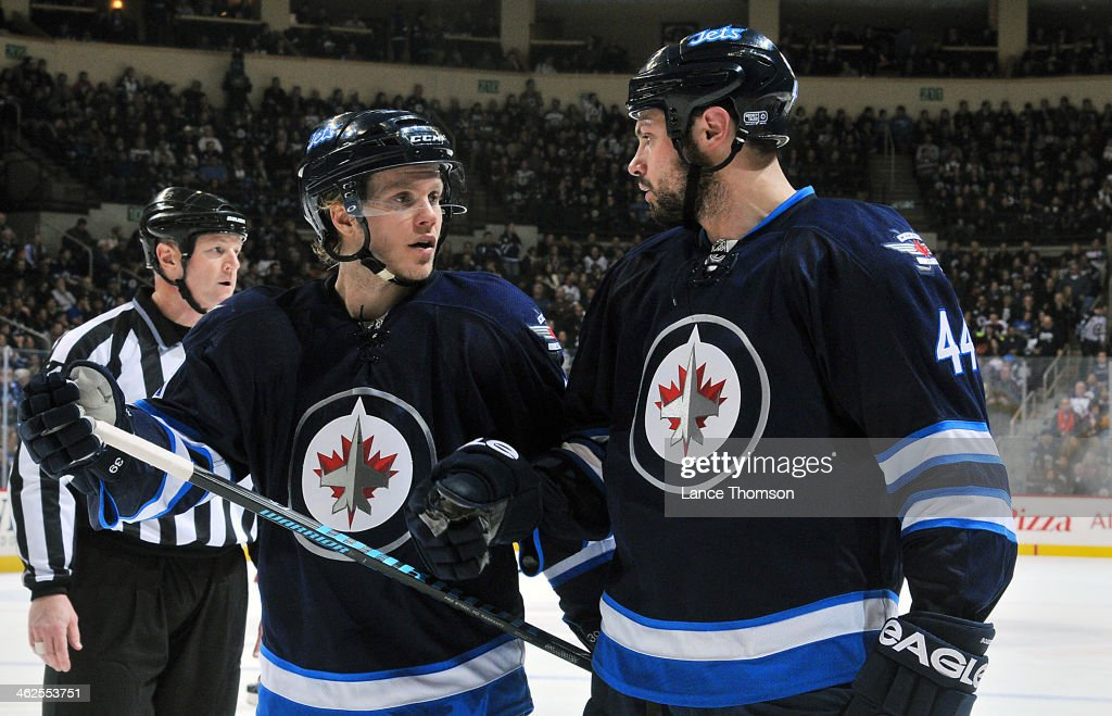 Tobias Enstrom #39 and Zach Bogosian #44 of the Winnipeg Jets discuss strategy during a third period stoppage in play in NHL action against the Phoenix Coyotes at the MTS Centre on January 13, 2014 in Winnipeg, Manitoba, Canada.