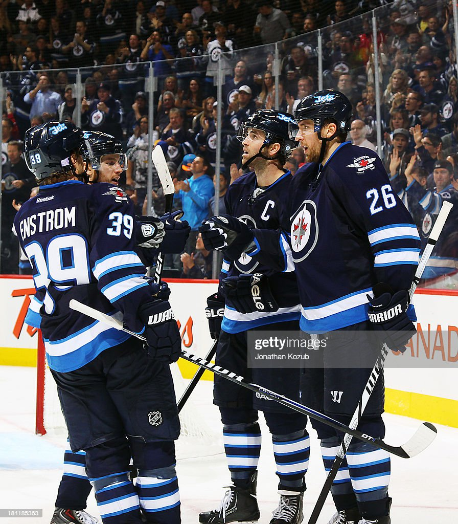 Tobias Enstrom #39, Bryan Little #18, Andrew Ladd #16 and Blake Wheeler #26 of the Winnipeg Jets celebrate a third period goal against the Dallas Stars at the MTS Centre on October 11, 2013 in Winnipeg, Manitoba, Canada.