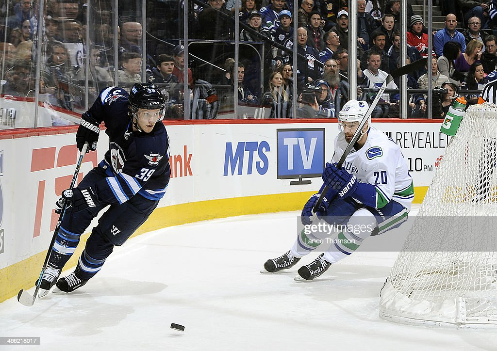 Tobias Enstrom #39 of the Winnipeg Jets passes the puck around the net as Chris Higgins #20 of the Vancouver Canucks gives chase during third period action at the MTS Centre on January 31, 2014 in Winnipeg, Manitoba, Canada.