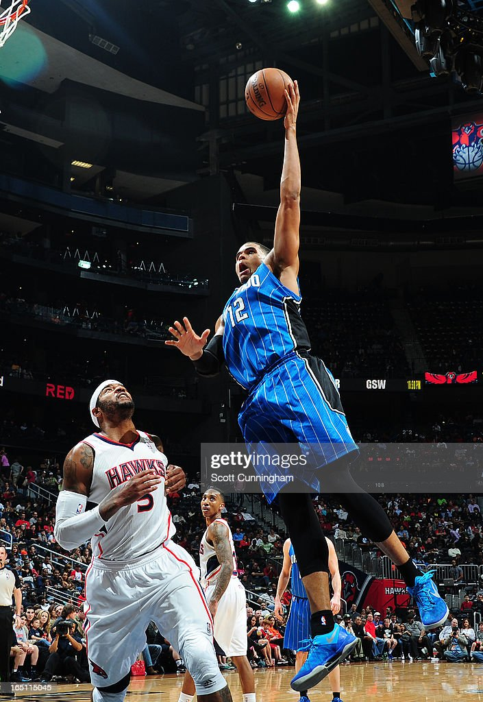 Tobias Harris #12 of the Orlando Magic glides to the basket against Josh Smith #12 of the Atlanta Hawks on March 30, 2013 at Philips Arena in Atlanta, Georgia.
