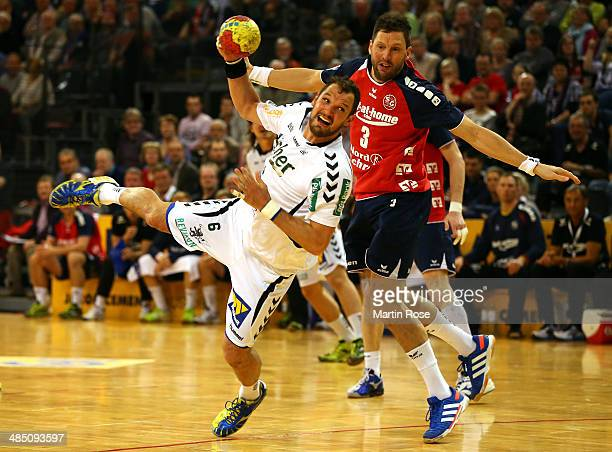 Tobias Karlsson of Flensburg challenges for the ball with Jens Tiedtke of Wetzlar during the DKB Bundesliga handball match between Flensburg...