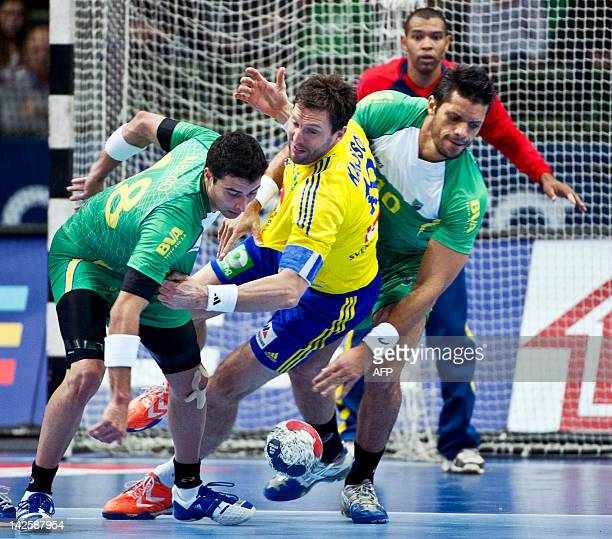 Tobias Karlsson of Sweden vies for the ball with Brazil's defenders Felipe Ribeiro and Gil Vicente Pires during their men's handball Olympic...