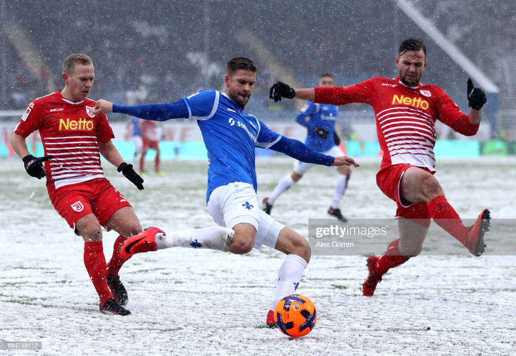 Tobias Kempe (C) of Darmstadt and Alexander Nandzik (L) and Benedikt Gimber of Regensburg battle for the ball during the Second Bundesliga match between SV Darmstadt 98 and SSV Jahn Regensburg at Jonathan-Heimes-Stadion am Boellenfalltor on December 3, 2017 in Darmstadt, Germany.