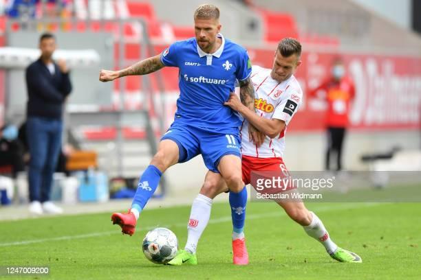 Tobias Kempe of Darmstadt is challenged by Benedikt Saller of Regensburg during the Second Bundesliga match between SSV Jahn Regensburg and SV...