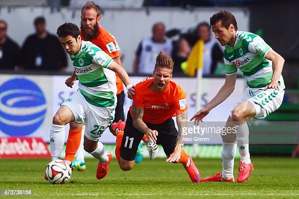 Tobias Kempe of Darmstadt is challenged by Zhi Gin Lam and Goran Sukalo of Greuther Fuerth during the Second Bundesliga match between SpVgg Greuther...