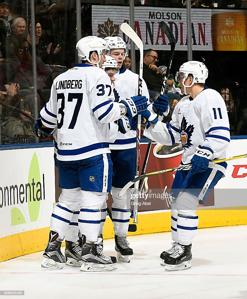 Tobias Lindberg #37, Andrew Nielsen #6 and Andreas Johansson #11 celebrate with Colin Smith #9 of the Toronto Marlies during game action against the Utica Comets on November 26, 2016 at Air Canada Centre in Toronto, Ontario, Canada.