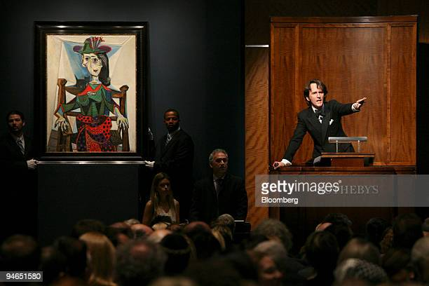 """Tobias Meyer, global head of contemporary art and today's auctioneer for Sotheby's Inc., acknowledges bids for Pablo Picasso's painting """"Dora Maar au..."""