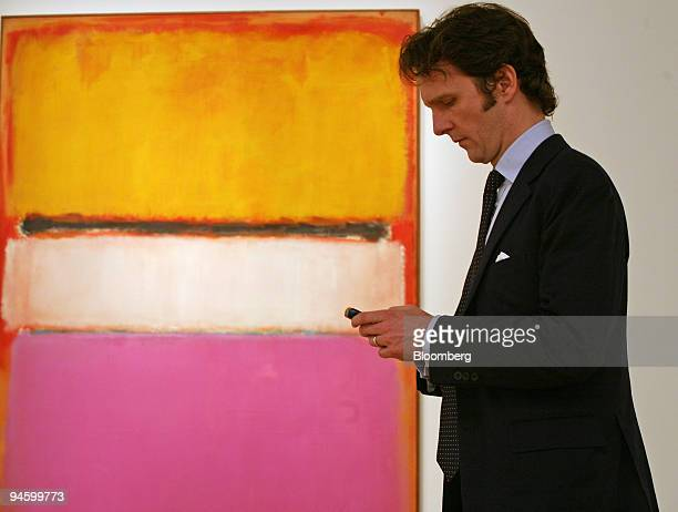 Tobias Meyer global head of contemporary art for Sotheby's works on his PDA while standing beside Mark Rothko's White Center at Sotheby's on Friday...