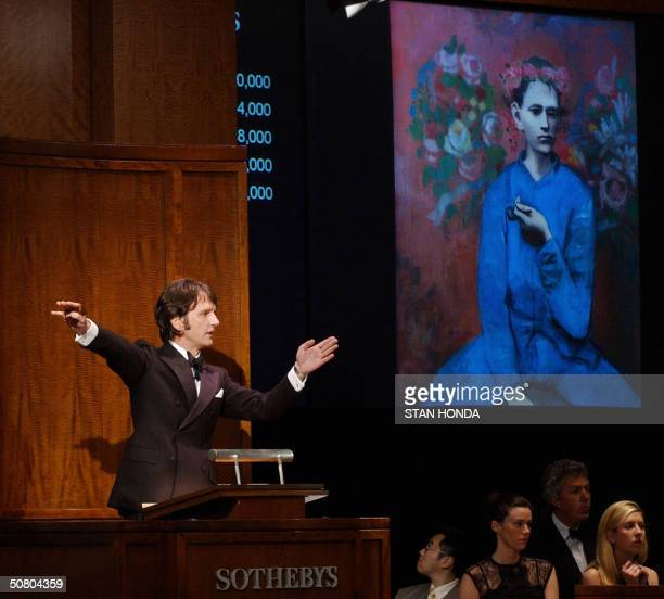 Tobias Meyer of Sotheby's points to bidders during the sale of Pablo Picasso's Garcon a la Pipe which eventually sold for USD 104000 a record price...