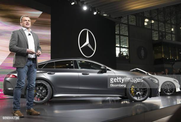 Tobias Moers chief executive officer of MercedesBenz AMG speaks while standing next to the Daimler AG MercedesBenz AMG GT 63 S vehicle left during...