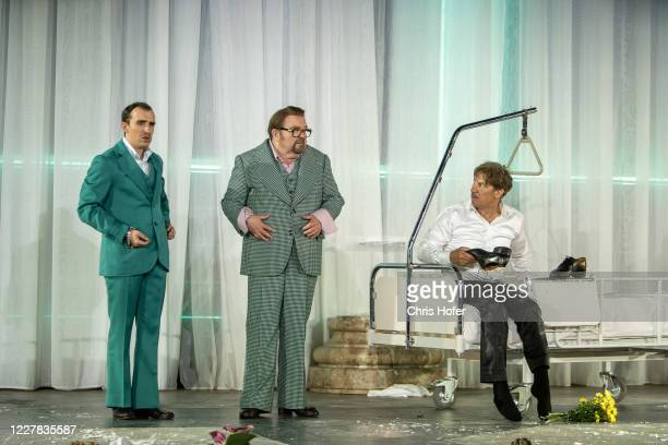 """Tobias Moretti as """"Jedermann"""", Gustav Peter Woehler as """"Dicker Vetter"""" and Tino Hillebrand as """"Duenner Vetter"""" performing on stage during the outdoor..."""