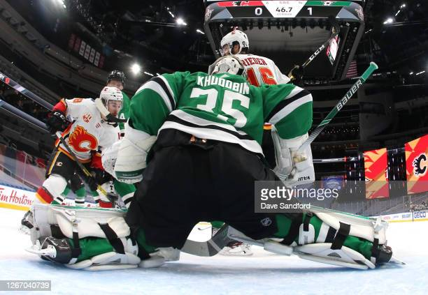 Tobias Rieder and Oliver Kylington of the Calgary Flames watch as the puck gets past goaltender Anton Khudobin of the Dallas Stars on a goal by...