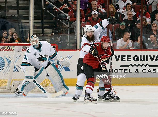 Tobias Rieder of the Arizona Coyotes and Brent Burns of the San Jose Sharks battle for position in front of goalie Martin Jones of the Sharks during...