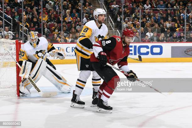 Tobias Rieder of the Arizona Coyotes and Brian Dumoulin of the Pittsburgh Penguins battle for position in front of goalie Matthew Murray of the...