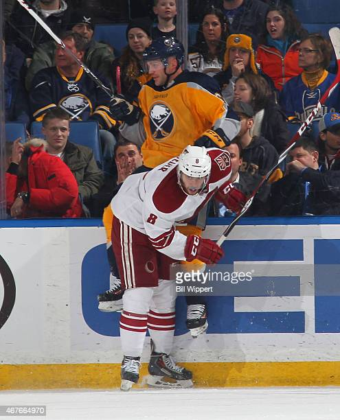 Tobias Rieder of the Arizona Coyotes checks Andre Benoit of the Buffalo Sabres on March 26 2015 at the First Niagara Center in Buffalo New York