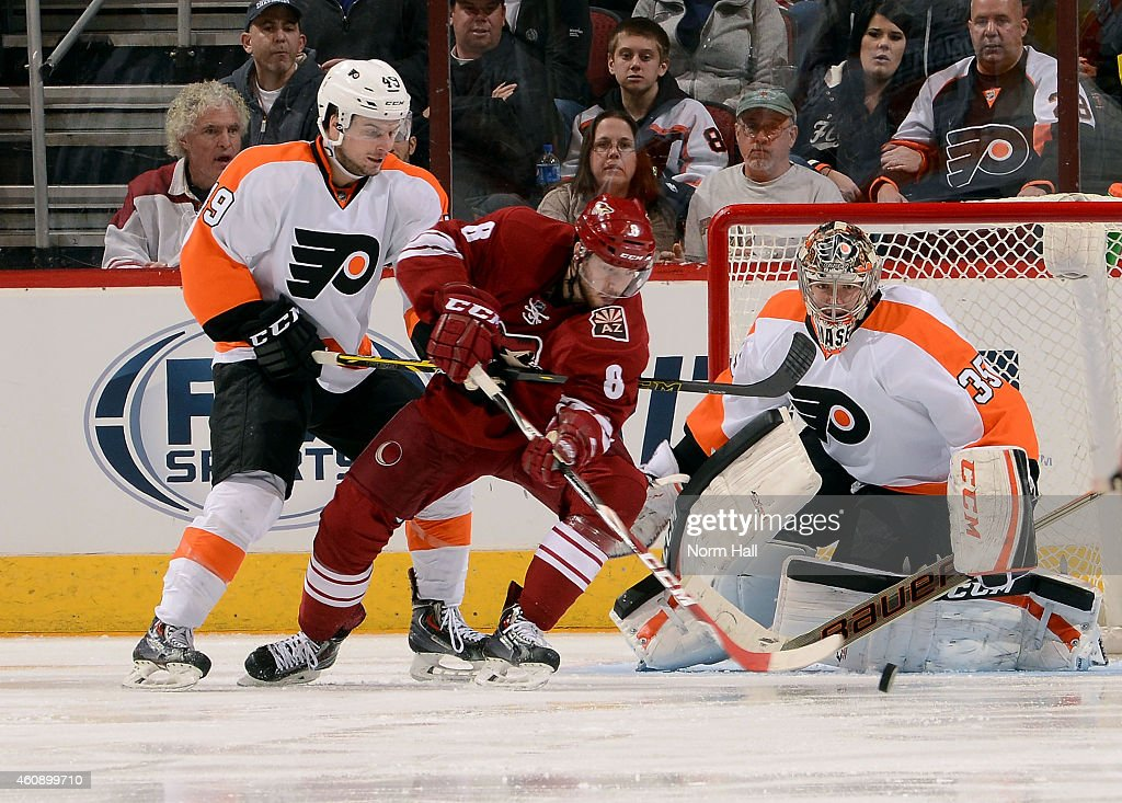 Tobias Rieder #8 of the Arizona Coyotes looks to get a shot off in front of goaltender Steve Mason #35 of the Philadelphia Flyers as Scott Laughton #49 of the Flyers defends during the third period at Gila River Arena on December 29, 2014 in Glendale, Arizona.
