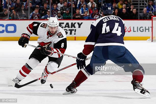 Tobias Rieder of the Arizona Coyotes pushes the puck past Eric Gelinas of the Colorado Avalanche at Pepsi Center on March 7 2016 in Denver Colorado