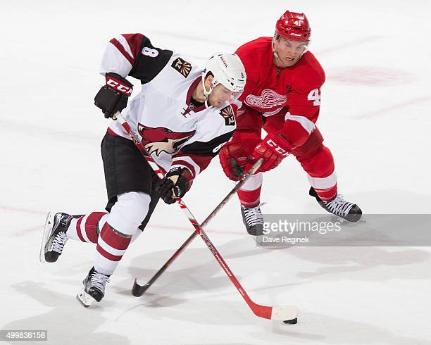 Tobias Rieder of the Arizona Coyotes skates up ice with the puck past Luke Glendening of the Detroit Red Wings during an NHL game at Joe Louis Arena...