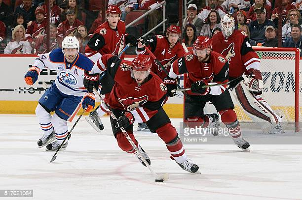 Tobias Rieder of the Arizona Coyotes skates with the puck ahead of Jordan Eberle of the Edmonton Oilers during the first period at Gila River Arena...