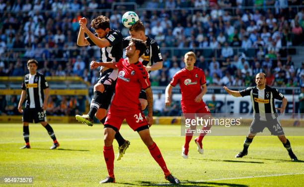 Tobias Strobl of Moenchengladbach and Nico Elvedi of Moenchengladbach go up for a header with Tim Kleindienst of Freiburg during the Bundesliga match...