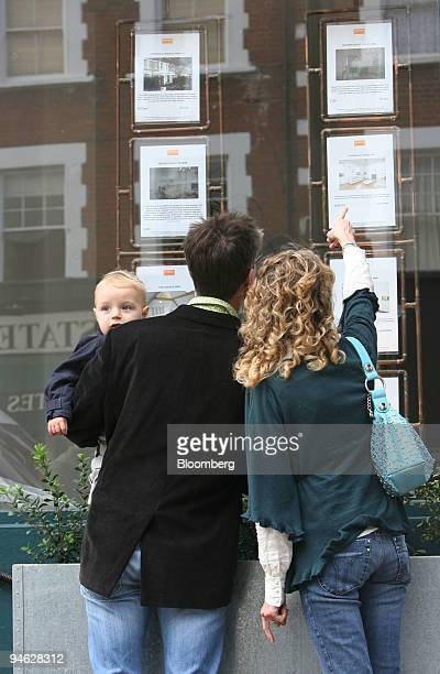 Tobias Till left holds his son Jacob Till as he and his wife Cynthia Westwood look at property for sale in the windows of an estate agents shop in...