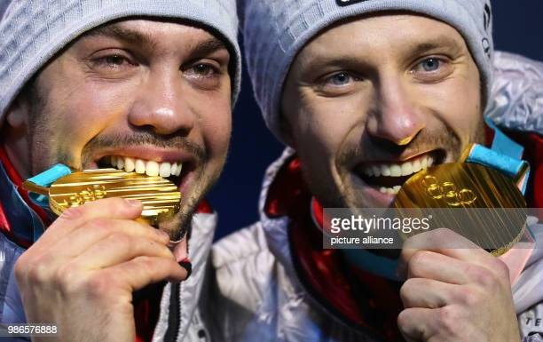 Tobias Wendl and Tobias Arlt fromGermany biting their gold medals during the award ceremony of the team luge event of the 2018 Winter Olympics in...