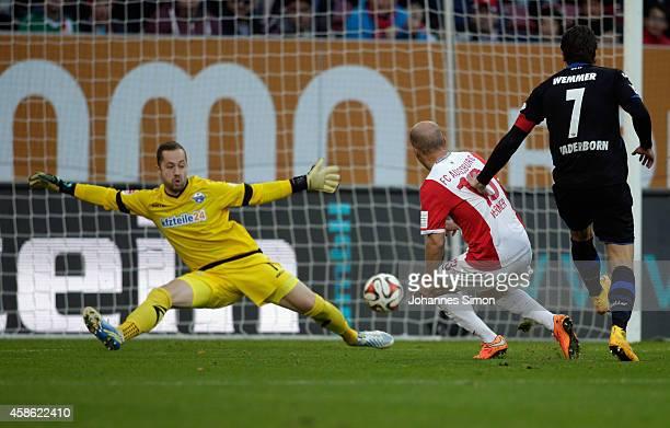 Tobias Werner of Augsburg scores his team's first goal against Lukas Kruse goalkeeper of Paderborn during the Bundesliga match between FC Augsburg...