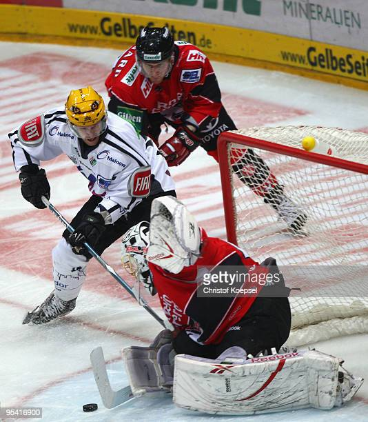 Tobias Woerle of Frankfurt Lions shoots the puck and Lars Weibel of the Haie saves the puck during the DEL match between Koelner Haie and Frankfurt...