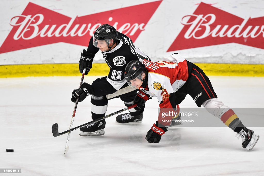 Tobie Paquette-Bisson #12 of the Blainville-Boisbriand Armada skates the puck against Christopher Benoit #21 of the Baie-Comeau Drakkar during the QMJHL game at Centre d'Excellence Sports Rousseau on November 24, 2017 in Boisbriand, Quebec, Canada.