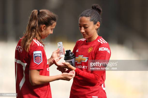 Tobin Heath and Christen Press of Manchester United Women share a hand sanitiser during the warm down during the Covid-19 pandemic after the Barclays...