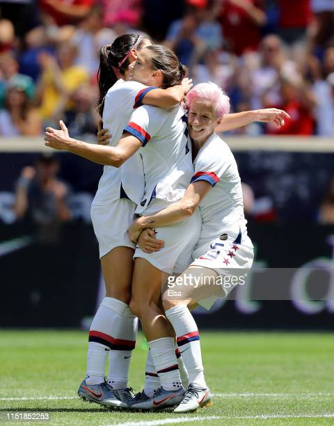 Tobin Heath of the United States is congratulated by teammates Megan Rapinoe and Alex Morgan after she scored in the first half against Mexico at Red...