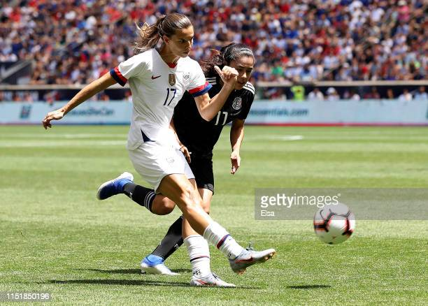 Tobin Heath of the United States takes a shot in the first half as Lizbeth Ovalle of Mexico defends at Red Bull Arena on May 26 2019 in Harrison New...
