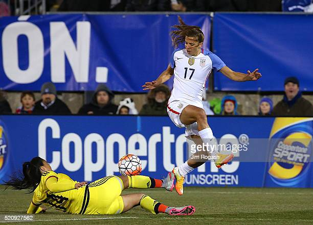 Tobin Heath of United States of America leaps over Nataly Arias of Colombia during an international friendly soccer match against the United States...