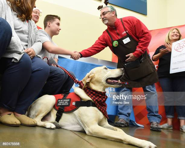 Toby 14yearold Parker Rogers' service dog sits patiently as Parker receives congratulation from Petco district leader Bill Houchins during a check...