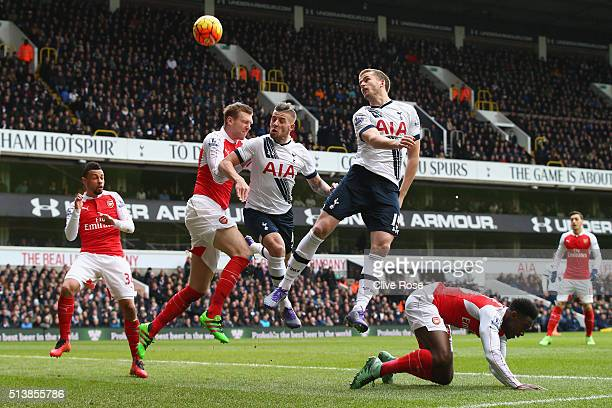 Toby Alderweireld and Eric Dier of Tottenham Hotspur jump with Per Mertesacker of Arsenal during the Barclays Premier League match between Tottenham...
