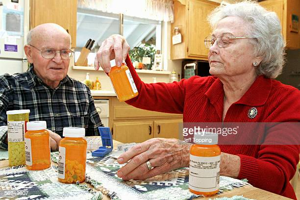 Toby Anderson watches as his wife Amy divides his eight prescription drugs into a weekly schedule at their home November 21 2005 in Sun City Arizona...