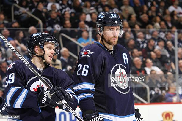 Toby Enstrom and Blake Wheeler of the Winnipeg Jets look on during a second period stoppage in play against the Nashville Predators at the MTS Centre...