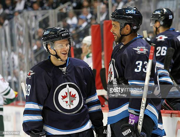Toby Enstrom and Dustin Byfuglien of the Winnipeg Jets share a laugh during a third period stoppage in play against the Minnesota Wild at the MTS...