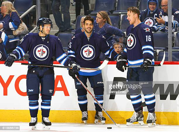 Toby Enstrom Mathieu Perreault and Shawn Matthias of the Winnipeg Jets share a laugh during the pregame warm up prior to NHL action against the...