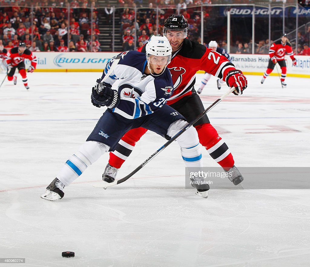 Toby Enstrom #39 of the Winnipeg Jets and Kyle Palmieri #21 of the New Jersey Devils battle for a loose puck during the game at the Prudential Center on October 9, 2015 in Newark, New Jersey.