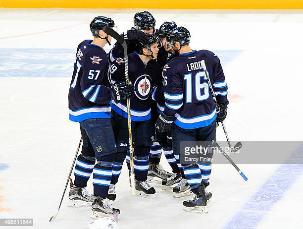 Toby Enstrom of the Winnipeg Jets gets congratulated for his first period goal against the Colorado Avalanche by teammates Tyler Myers Blake Wheeler...